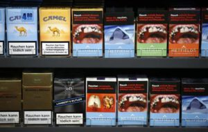 Cigarette boxes with an affixed, self-made cigarette label displaying graphic images and those with the original label are pictured in the shop of tobacconist and kiosk owner Schulzki in Berlin